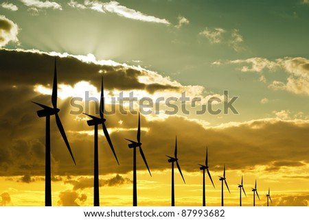Wind turbines at sunset - stock photo