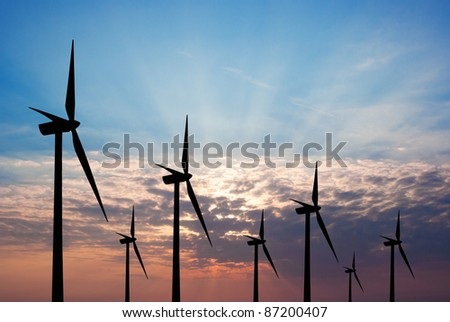 Wind turbines at the sunset - stock photo