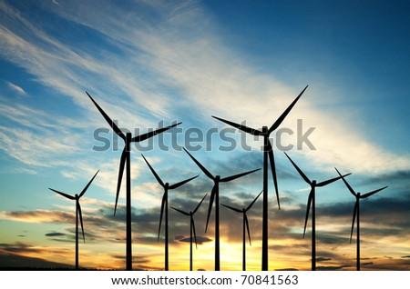 Wind turbines farm at sunset - stock photo