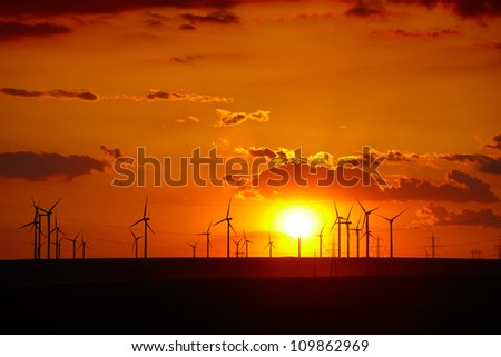 Wind turbines farm at sunset in Dobrogea region of Romania. - stock photo