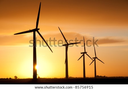 Wind turbines farm by sunrise - stock photo