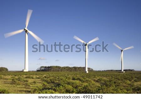 Wind turbines farm generating clean electricity over plain land. Alternative energy source - stock photo
