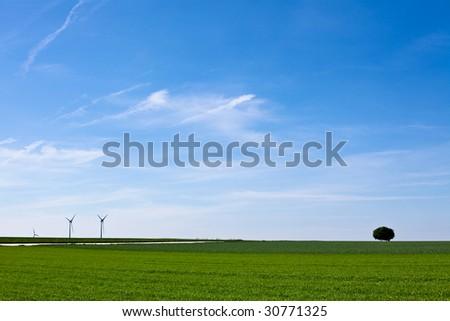 Wind turbines farm in green field over cloudy sky - stock photo