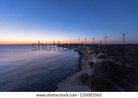 wind turbines generating clean power with lighthouse at blue hours - stock photo