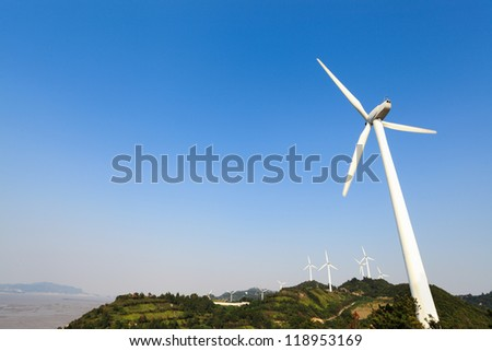 wind turbines generating electricity in wind farm at the beach - stock photo