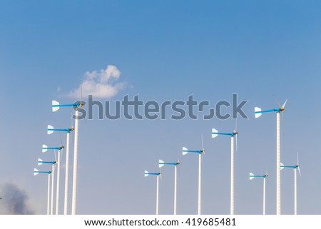 Wind turbines generating electricity on blue sky - stock photo