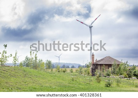 Wind turbines in a country side with a barn and a garden nearby. Eco life concept. - stock photo