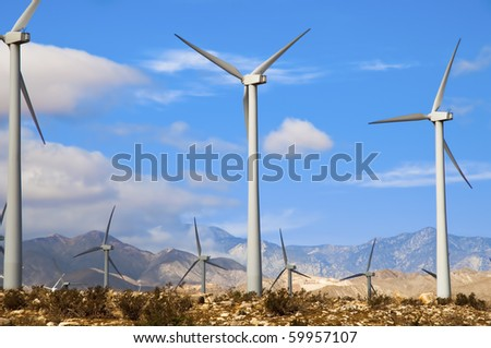 Wind turbines in a desert setting with mountains in the background - stock photo