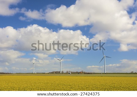 Wind turbines in a field of fresh yellow flowers in spring - stock photo