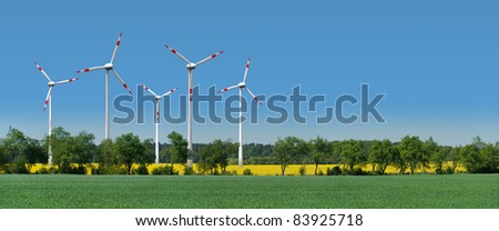 Wind turbines in a rapeseed field behind an alley - stock photo