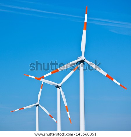 Wind turbines in a row against clear blue sky - stock photo