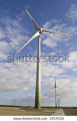 Wind turbines in an agricultural field against a blue with white sky