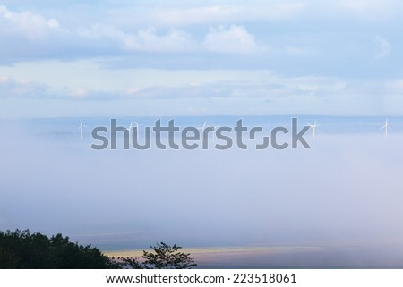 Wind turbines in foggy landscape - stock photo