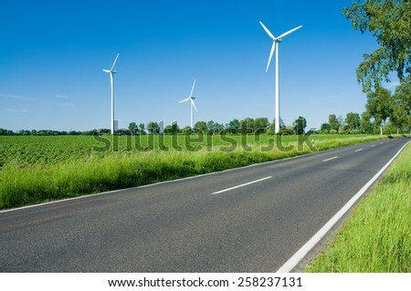 Wind turbines in green landscape beside a road against blue sky, alternative energy, new natural scenery