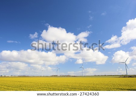 Wind turbines in Holland in a field of fresh yellow flowers in spring - stock photo