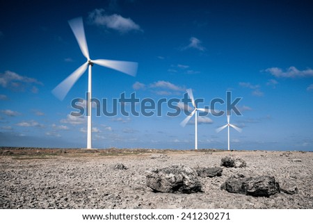 Wind turbines in rocky desert - stock photo