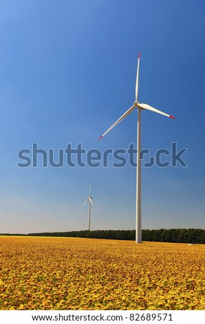 Wind turbines in sunflower field against blue sky
