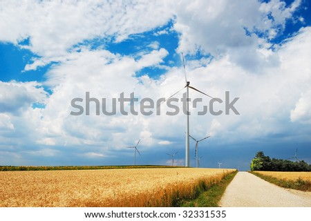 Wind turbines in sunflowers and wheat field - stock photo