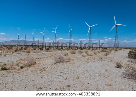 Wind turbines in the desert on a windy day - stock photo