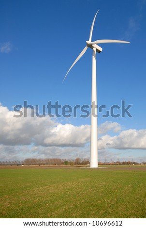 Wind Turbines in the grass with blue cloudy sky - stock photo