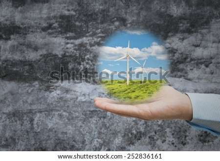 Wind turbines in the meadow held by hand - stock photo