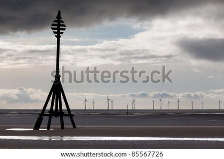 Wind turbines in the ocean off a sandy beach near Liverpool on a cold and cloudy day
