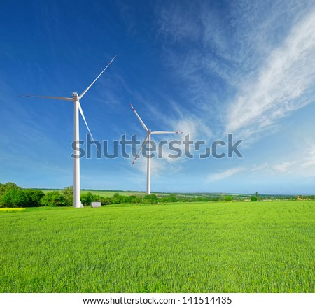 wind turbines on a beautiful green field of young wheat