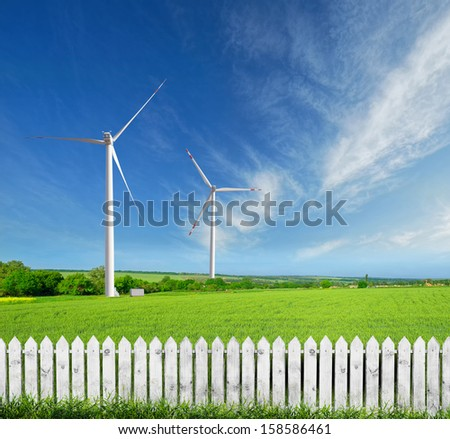 wind turbines on a beautiful green field of young wheat - stock photo