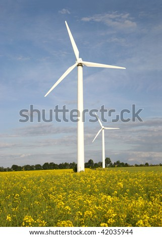 Wind turbines on a brilliant rapeseed field