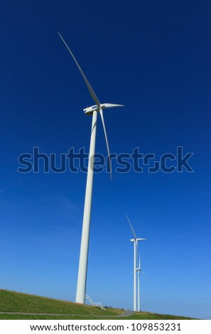 Wind turbines on a dyke generating clean and renewable energy.