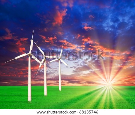 wind turbines on a green field by a sunset - stock photo