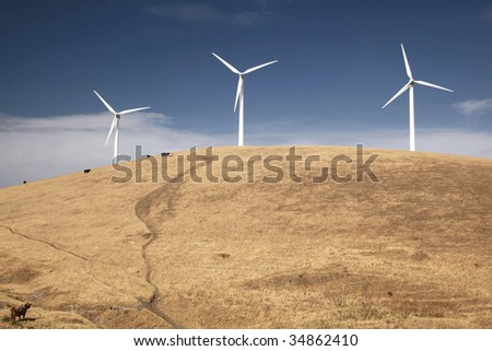 Wind turbines on a hill, with cows grazing and pretty clouds in the sky.