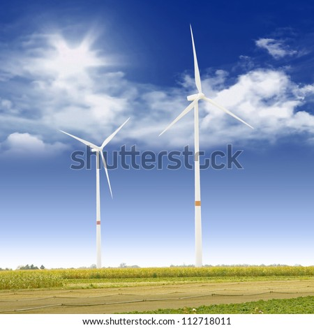 wind turbines on a sunny day with field in front