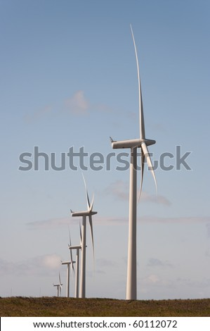 Wind turbines on a wind farm in Scotland, Europe. The sun is setting on a summer evening. - stock photo