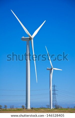 wind turbines on bright sunny day next to electricity pylons - stock photo