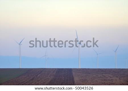 wind turbines on field on foggy morning - stock photo