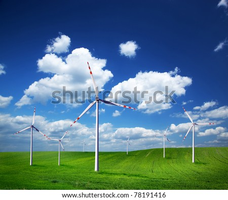 Wind turbines on green field. Natural energy power - stock photo