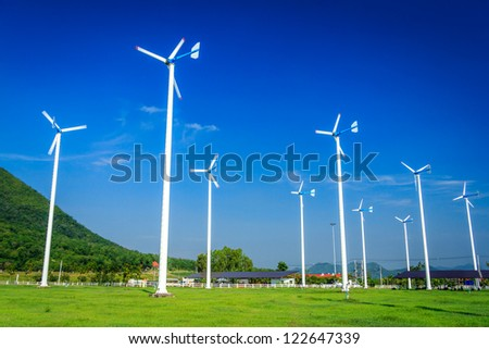 Wind Turbines On Green Garden