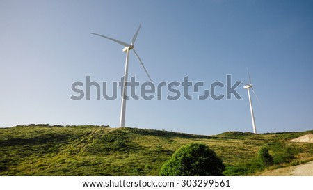 Wind turbines on hills generating electricity over a blue sky background. Clean and ecological energy production concept.