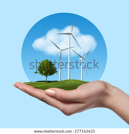 Wind turbines on meadow with tree holds in woman hand against blue sky and clouds. Green energy concept - stock photo
