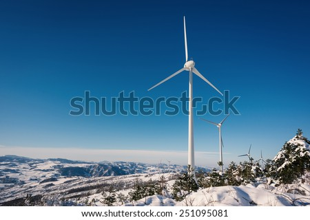 Wind turbines on snow winter landscape with dark blue sky. - stock photo