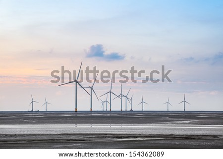 wind turbines on the coastal mud flat in sunset - stock photo