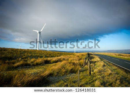 Wind turbines on the green grass over the blue clouded sky - stock photo
