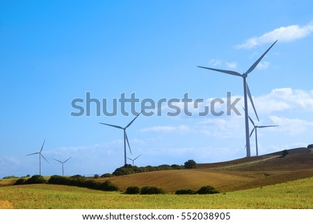 Wind turbines on the green hills of Andalusia at the midday