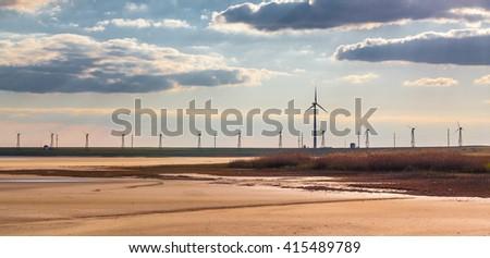 Wind turbines on the horizon before sunset - stock photo