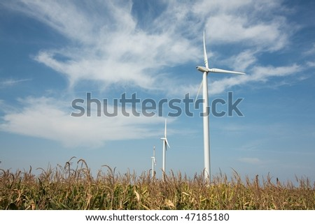 Wind turbines over an agricultural field - stock photo