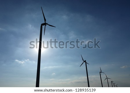 Wind turbines over blue sky with sun
