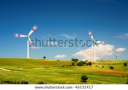 Wind turbines over cultivated fields - stock photo