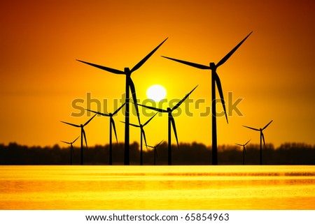 Wind turbines over sunset - stock photo