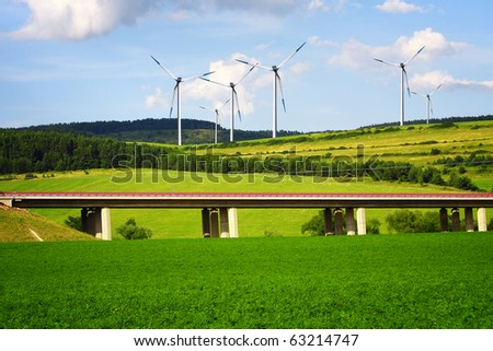 Wind turbines over the highway - stock photo